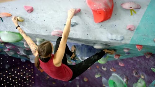 Female Athlete Training on Indoor Climbing Wall with Overhang