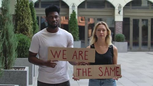A African American Man and a White Woman Stand on the Street Holding Posters for WE ARE and THE SAME