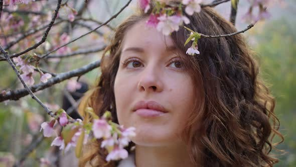 Closeup Portrait of Pretty Girl in Park with Blooming Japanese Sakura Trees