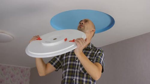 A Man Installs a Modern Led Ceiling Light on the Ceiling