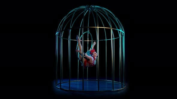 Thumbnail for Artist on the Gymnastic Hoop Performs Tricks in a Cage on the Stage in the Dark