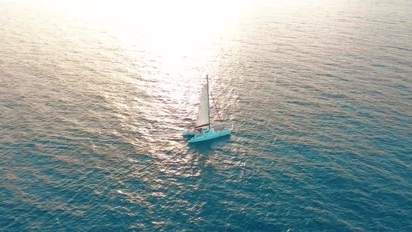 Aerial View. Catamaran Goes By Sea, Camera Move Closer and Fly Over Vessel, on the Sunset, Beautiful