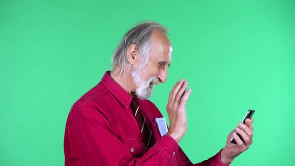 Portrait of Happy Old Aged Man 70s Talking for Video Chat Using Mobile Phone, Isolated Over Green