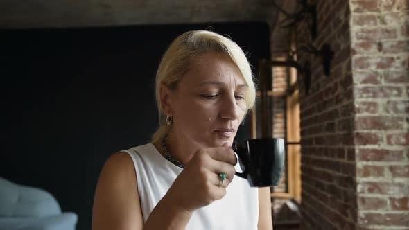 Thumbnail for Beautiful older woman is drinking coffee sitting near window