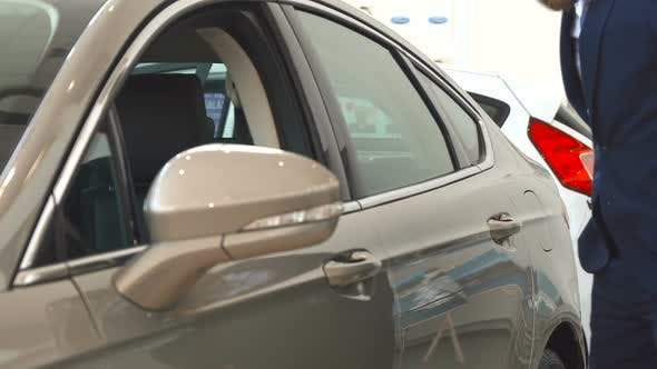 Thumbnail for Man Examines the Car at the Dealership