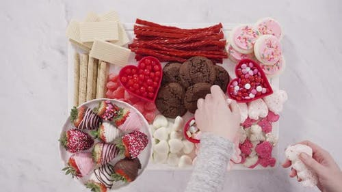 Flat lay. Step by step. Arranging cheese board with candies and cookies for Valentines Day.