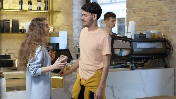 Young Positive Man and Woman Standing and Talking Waiting for Coffee in Cafe