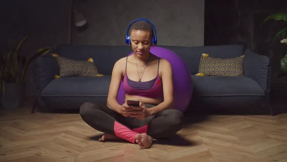Sporty Woman Text Messaging on Phone at Home