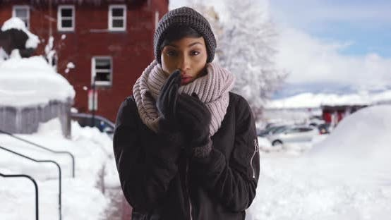 Cover Image for Young black woman standing on snowy street, blowing into her hands to warm up