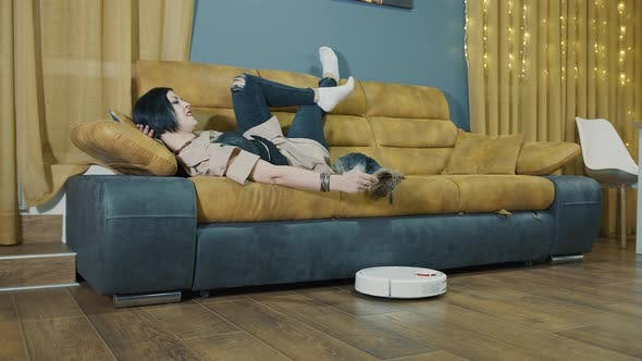 Woman Lying on the Couch with a Dog Turns on the Hand of a Robot Vacuum Cleaner
