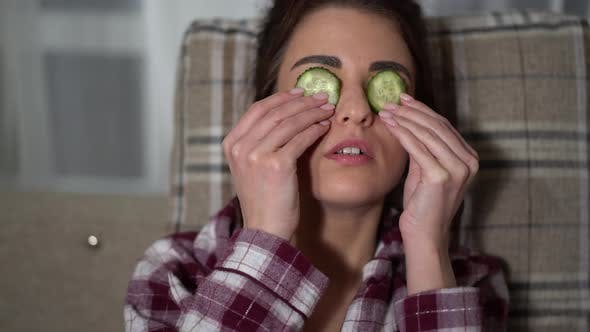 Thumbnail for Portrait of Pretty Young Woman in Pajama Making Eye Mask From Cucumbers in Cozy Evening, Chilling