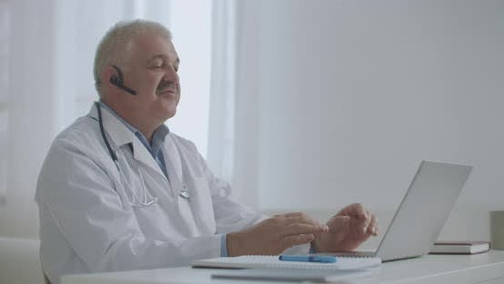 Physician Is Consulting Online, Sitting in Office of Private Clinic, Using Laptop for Talking with
