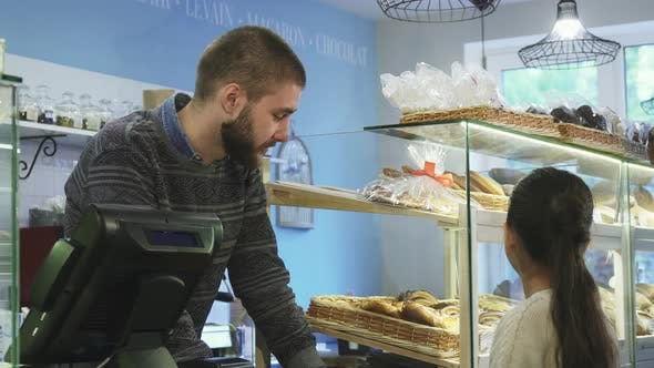 Thumbnail for Young Male Baker Working at His Store Helping Little Girl Choosing Desserts
