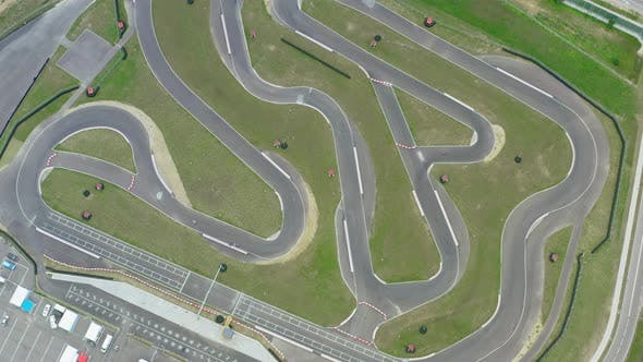 Thumbnail for Aerial Top Down View Drone Flies Over Racing Cars Driving on Winding Race Track. Cloudy Summer Day