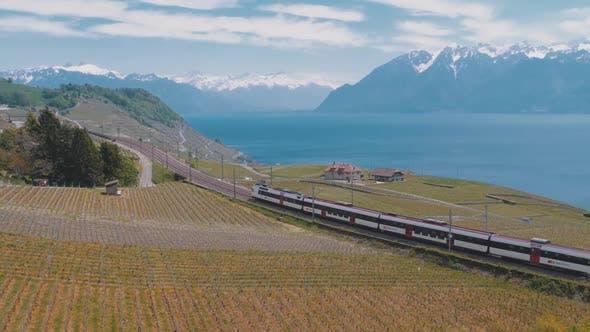 Thumbnail for Swiss Train Moves Along a Scenic Railway on a Hillside Near Lake Geneva Against of Alps, Switzerland