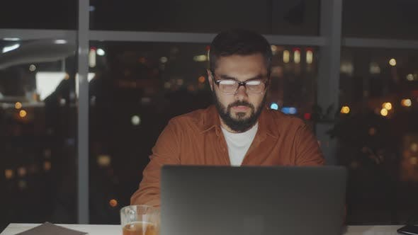 Thumbnail for Businessman Working on Laptop in Dark Office in Evening