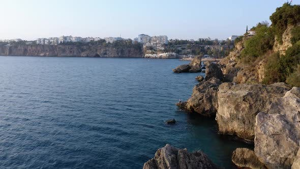 Top View of Rocky Cliffs Over Tuquoise Sea Water