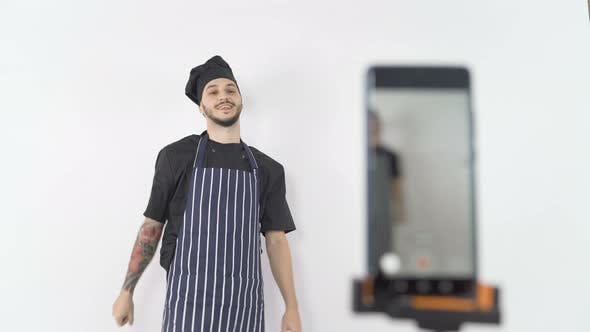Smiling Professional Male Chef in Apron and Hat Ending Online Lesson Streamed on Smartphone