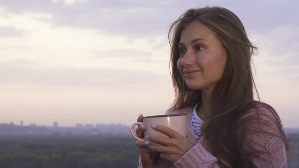 Thumbnail for A Young Girl Drinks a Warm Drink and Enjoys the Sunset
