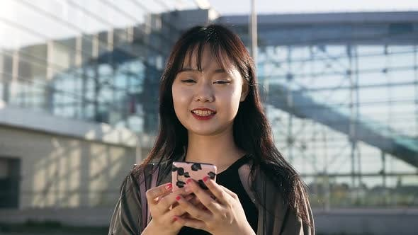 Thumbnail for Happy Asian Brunette with Long Hair Holding Her Phone and Looking at Camera