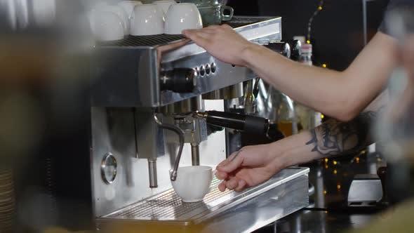 Thumbnail for Tattooed Barista Brewing Americano on Coffee Machine