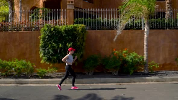 Woman Runs Down the Street Among the Palm Trees