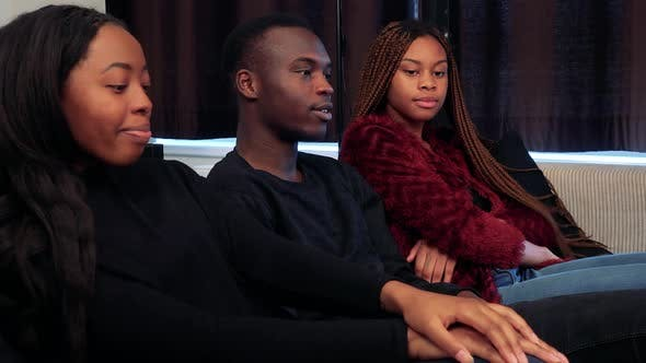 Thumbnail for African Man Watches Television and Two African Girls Come To Watch TV with Him and They Are Talking