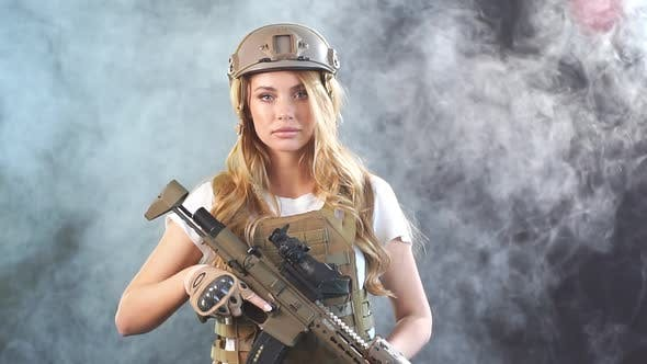 Thumbnail for Cute Sniper Woman with Rifle in Hands Standing in Military Outfit in Darkness