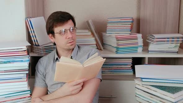 Thumbnail for Young Brunet Man in Glasses Reads a Book and Thinks Sitting Among Books