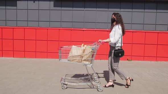 Thumbnail for Slowmo of Woman in Face Mask Walking with Cart of Groceries Outdoors