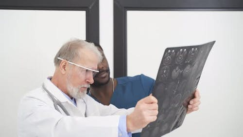 Two Doctors Looking At Computed Tomography Xray Image Discussing