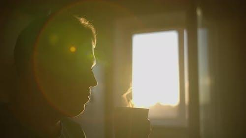 Silhouette of a man with a mug of hot coffee, sun glare, camera movement