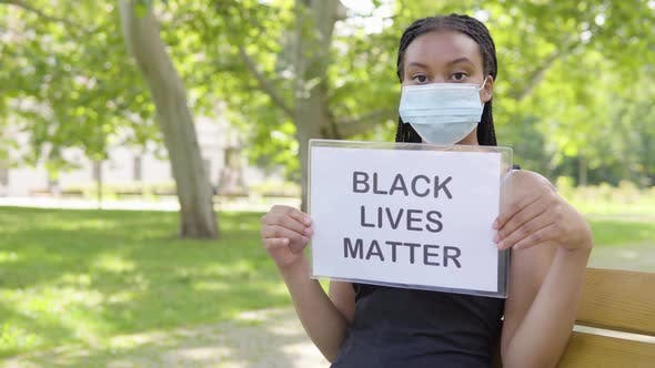 Thumbnail for A Young Black Woman in a Face Mask Shows a Black Lives Matter Sign To the Camera and Nods