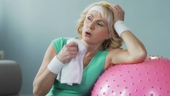 Thumbnail for Elderly female leaning on fitness ball fanning herself with towel, exhaustion