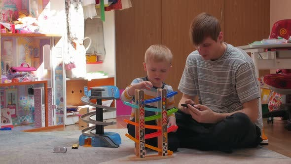 Son And Father Playing Cars