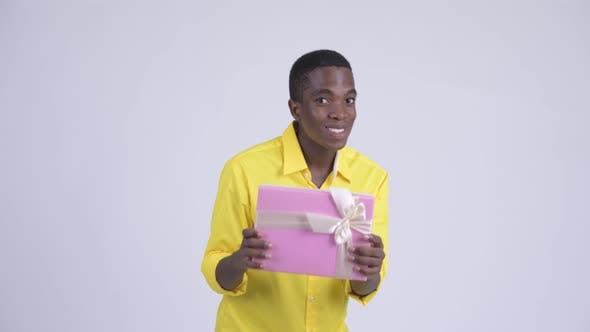 Thumbnail for Young Happy African Businessman Showing Gift Box with Surprise Gesture