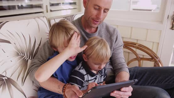 Dad looking at a tablet computer with his two sons going over school work form home