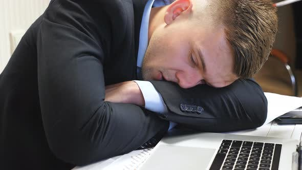 Close Up to Exhausted Boss in Formal Suit Falling Asleep on Table at Office