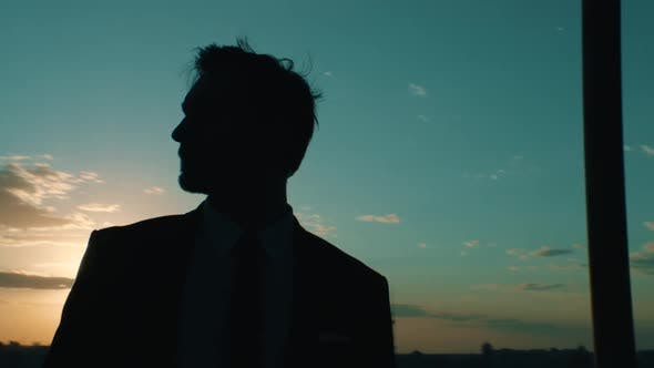 Thumbnail for Businessman on the Background of the City at Sunset