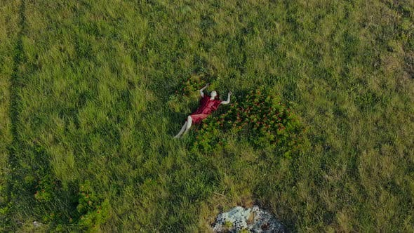 Background with Slow Motion and Aerial View of a Young Beautiful Woman in a Red Dress Who Lies in a