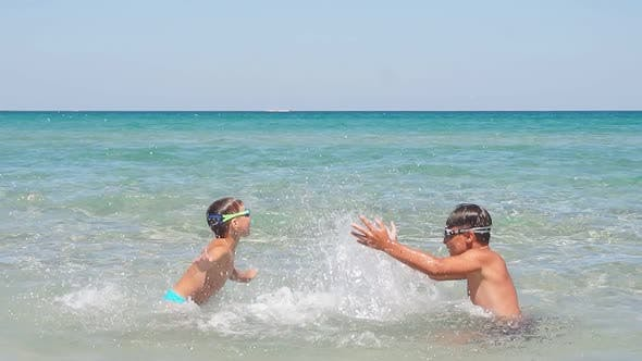 Children Boys Play in the Azure Turquoise Sea on a Sunny Day Creating a Splash of Water