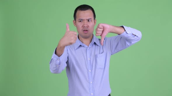 Thumbnail for Confused Asian Businessman Choosing Between Thumbs Up and Thumbs Down