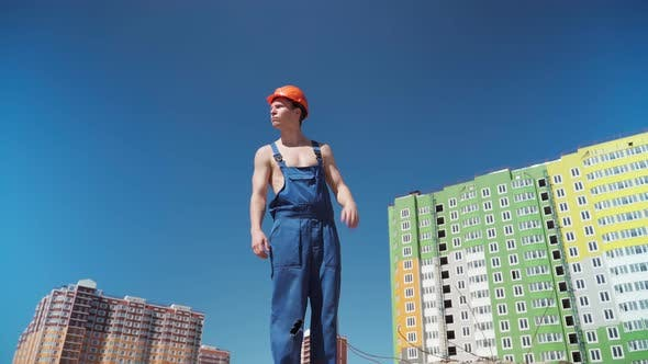 Serious Male Builder in Work Uniform and Hardhat Background of Buildings Under Construction.