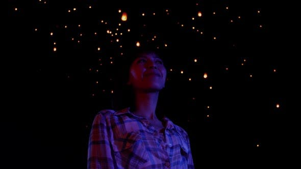 Thumbnail for Asian woman watches as sky lanterns fly Into the night sky