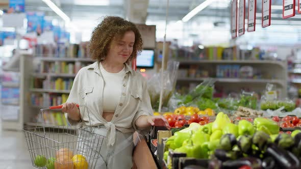 Thumbnail for Girl with Basket of Fresh Fruits Selects Vegetables at Supermarket Grocery Store