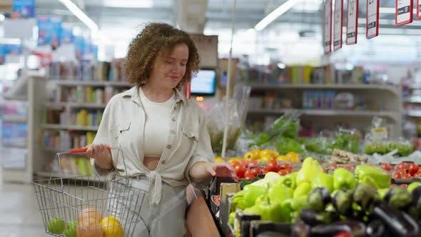 Thumbnail for Mädchen mit Korb von frischem Obst wählt Gemüse im Supermarkt Lebensmittelgeschäft