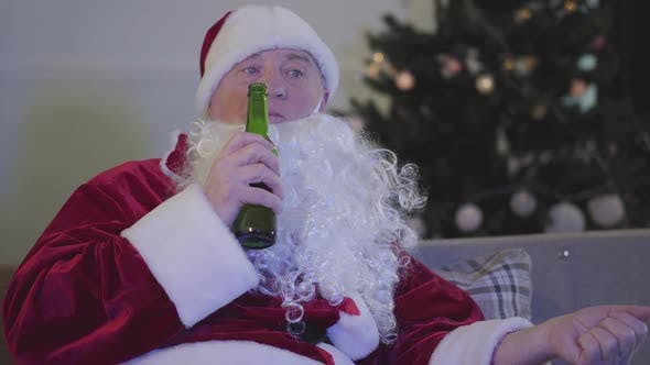 Cover Image for Close-up of Sad Caucasian Man in Santa Claus Costume Chewing and Drinking Beer. Bad Santa Claus