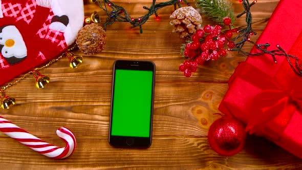 Thumbnail for Mannes Hand legt das Telefon auf den Tisch, Spielzeug liegt auf dem Tisch und Girlanden brennen. Ansicht von oben