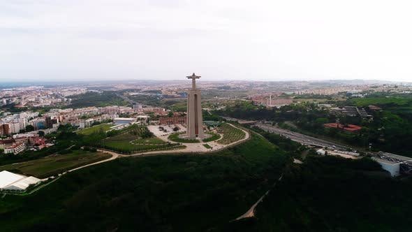 Majestic Jesus Monument Against White Cloudy Sky and Almada