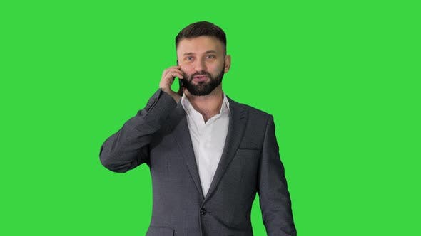 Thumbnail for Businessman Walking and Talking on Mobile Phone on a Green Screen, Chroma Key.